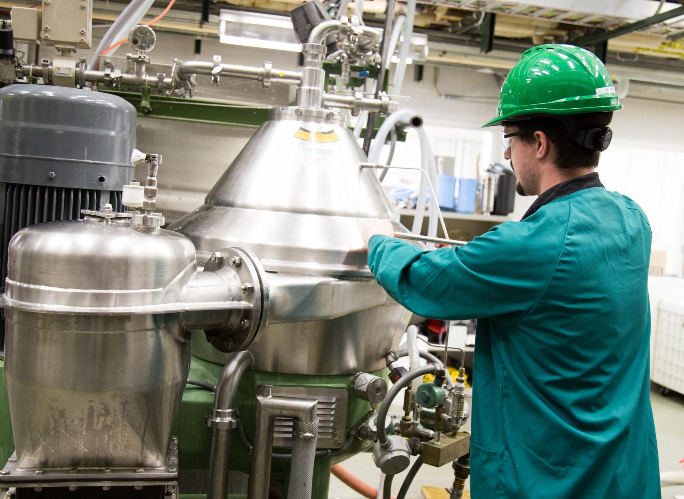 Lab staffer using disk stack centrifuge equipment