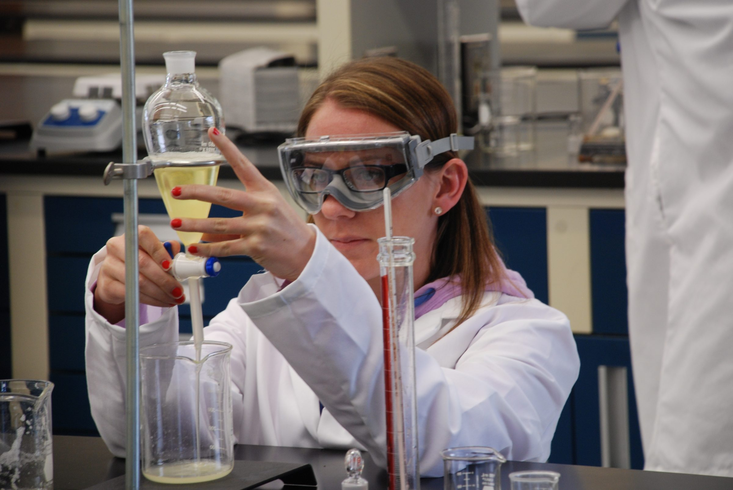 Woman working in a lab with chemicals on bench